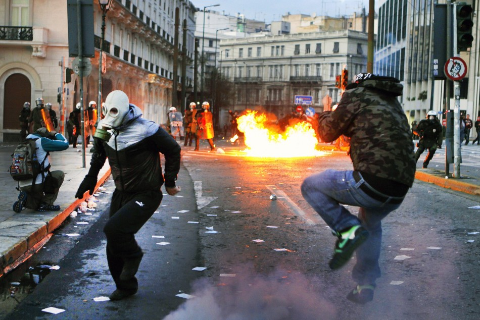 Protesters flee police after hurling petrol bombs at anti-austerity protests in Athens, unrest which has the potential to spread across Europe