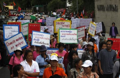 Female workers hold signs as they gather to mark International Womens Day outside the United Nations building in Bangkok