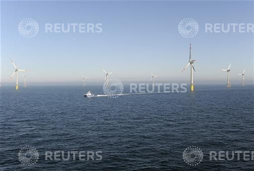 A service vessel passes next to wind energy plants in the offshore energy park Alpha Ventus in the North Sea