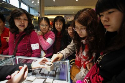 Chinese women look at jewelry during International Womens Day in Hong Kong