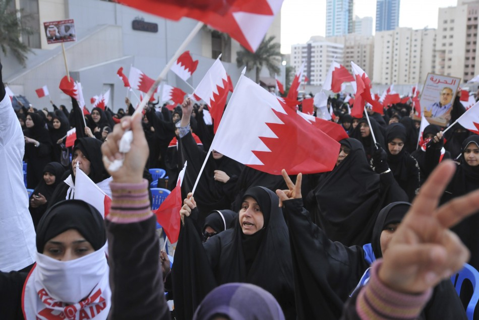 Bahraini protesters hold national flags during a demonstration outside the United Nations headquarters in Manama