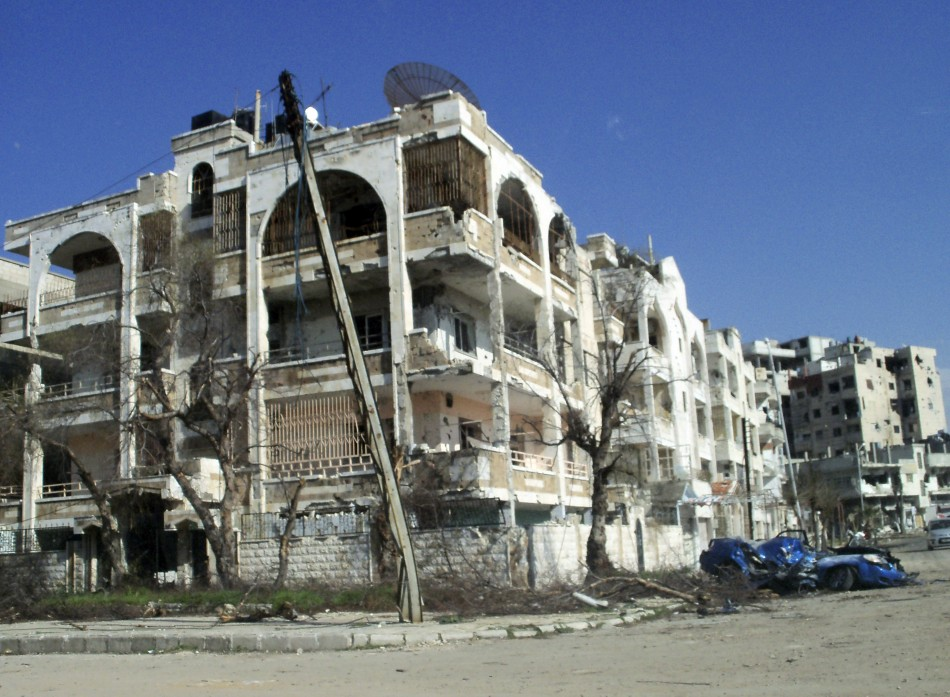 Damaged cars and houses are seen at Inshaat district of Homs