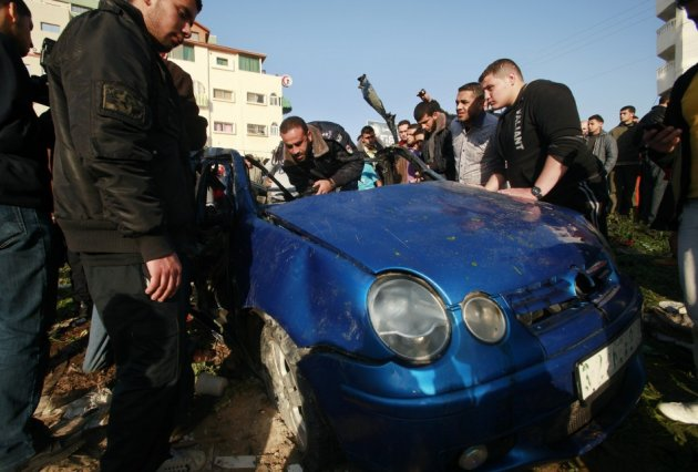 Hamas policemen inspect the remains of a vehicle after it exploded in Gaza City