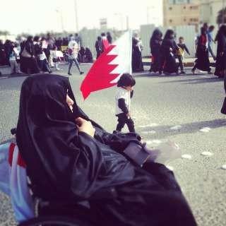 A child waving Bahrains flag walks as the demonstartion reach an end, while a women is sitting down.