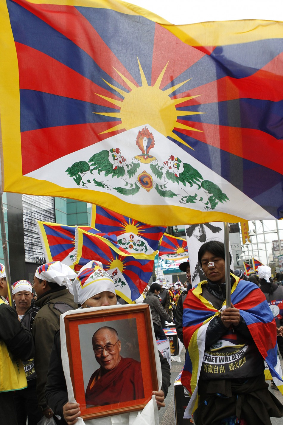 Activists holding a picture of the Dalai Lama and the Tibetan flags take part in a rally to support Tibet in Taipei