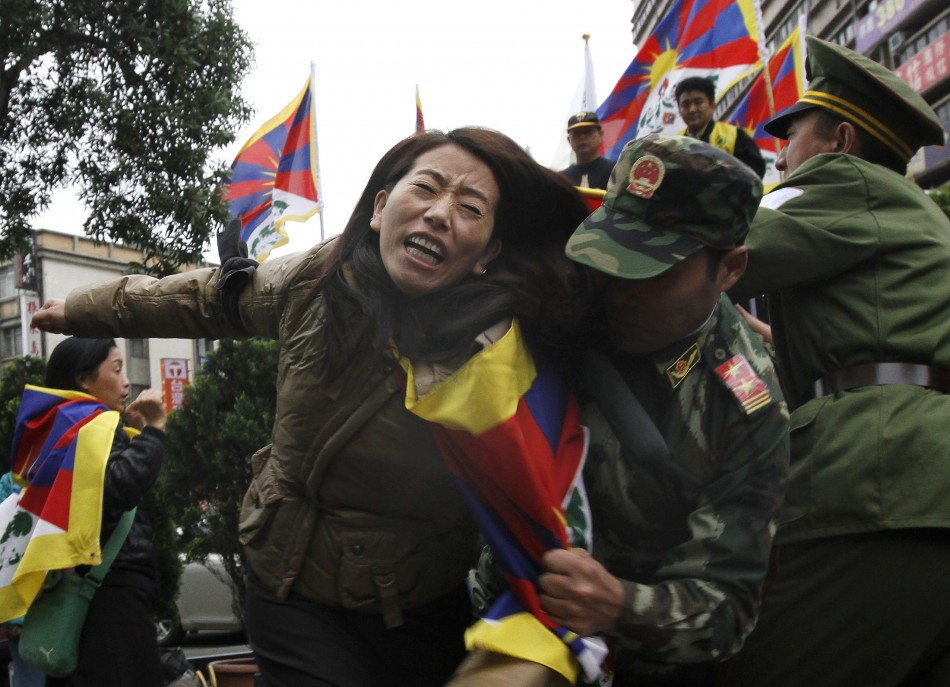 Activists dressed as Chinese soldiers and a Tibetan perform a street drama
