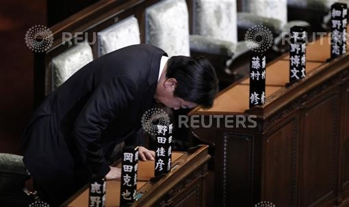 Japanese Prime Minister Yoshihiko Noda bows in the memory of his people