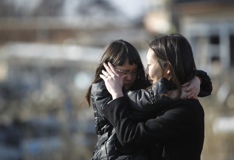 Kumagai and her mother Yoshiko cry as they visit the spot where their house, washed away by the March 11, 2011 tsunami, used to stand in Higashimatsushima