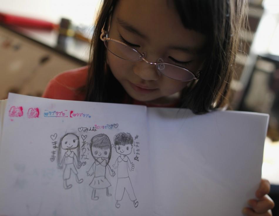Wakana Kumagai, 7, holds her illustration of her family in Higashimatsushima