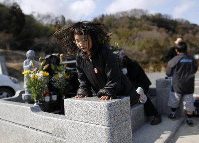 umagai, jumps on the grave of her father, who was killed by the tsunami, in Higashimatsushima, Miyagi prefecture