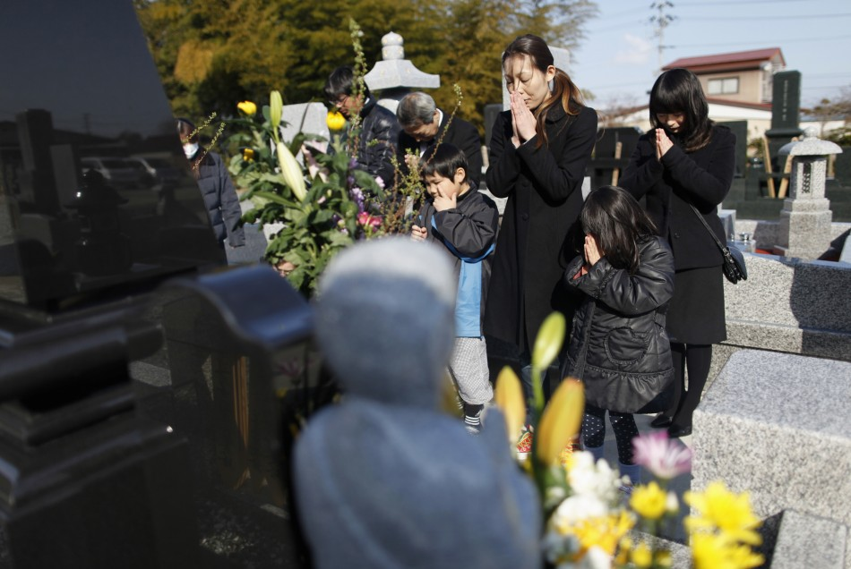 The family of a man who was killed by the tsunami observes a moment of silence at 246 p.m. in Higashimatsushima
