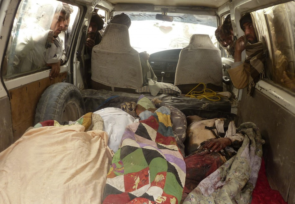 Afghan men look over the dead bodies of people killed by coalition forces in Kandahar province