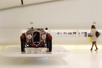 A woman walks near the 1934 Fiat 508 Coppa dOro Gold Cup at the Casa Enzo Ferrari museum during a media preview in Modena