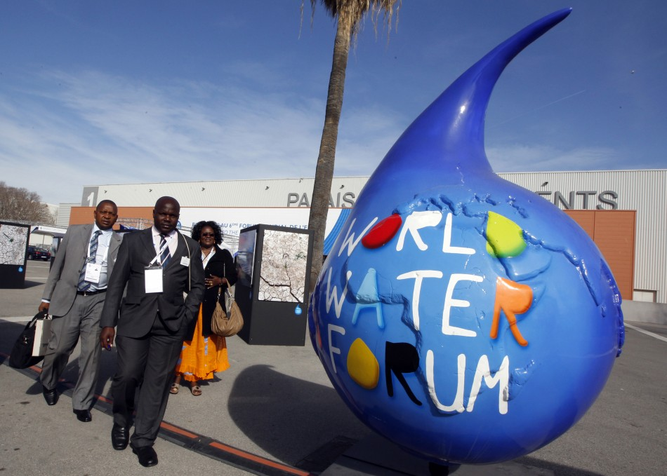 Participants walk past the logo of the 6th World Water Forum in Marseille