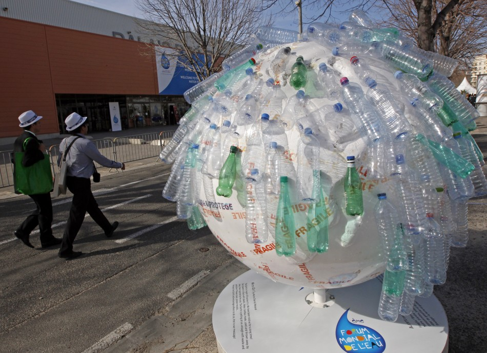 Participants walk past a globe decorated with plastic water bottles at the 6th World Water Forum in Marseille