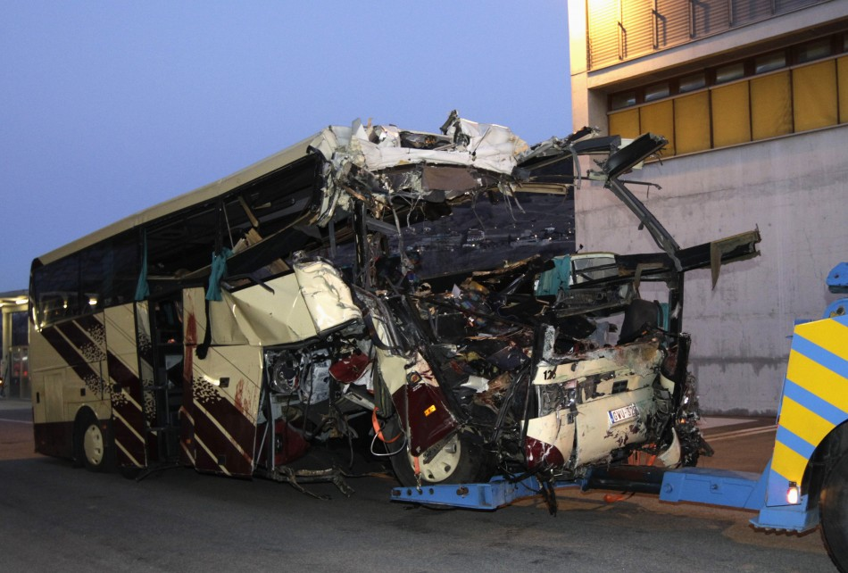 The wreckage of a bus that crashed into a motorway tunnel is pulled in Sierre, western Switzerland