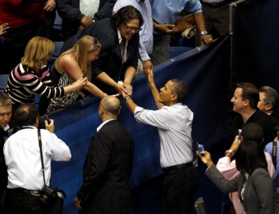 U.S. President Barack Obama greets supporters as he arrives with British PM David Cameron