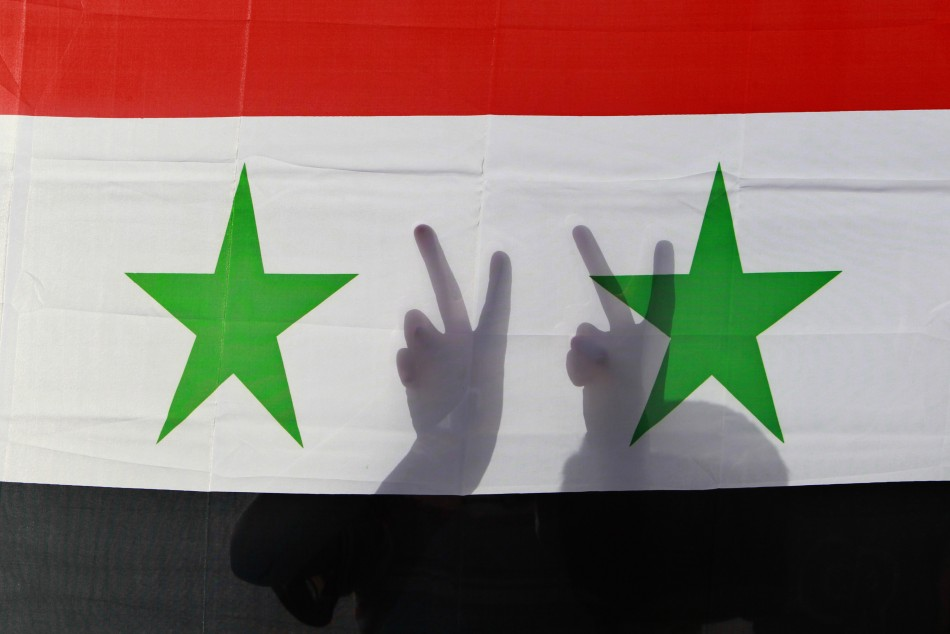 A Syrian protester gestures victory signs behind their national flag