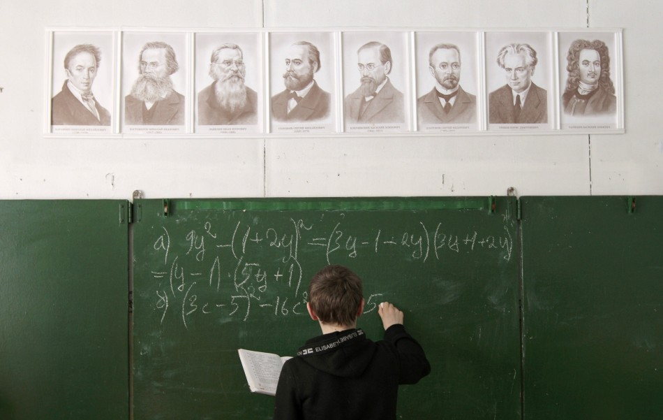 A pupil writes on the blackboard as he attends a mathematics lesson at a local school based in the remote Russian village of Bolshie Khutora