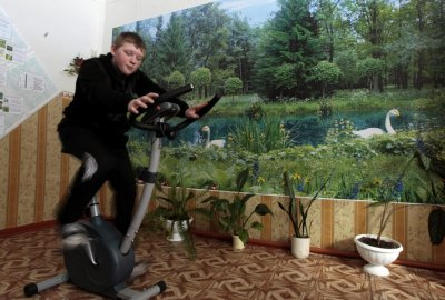 Boy rides an exercise bicycle at a school in the remote Russian village of Bolshie Khutora