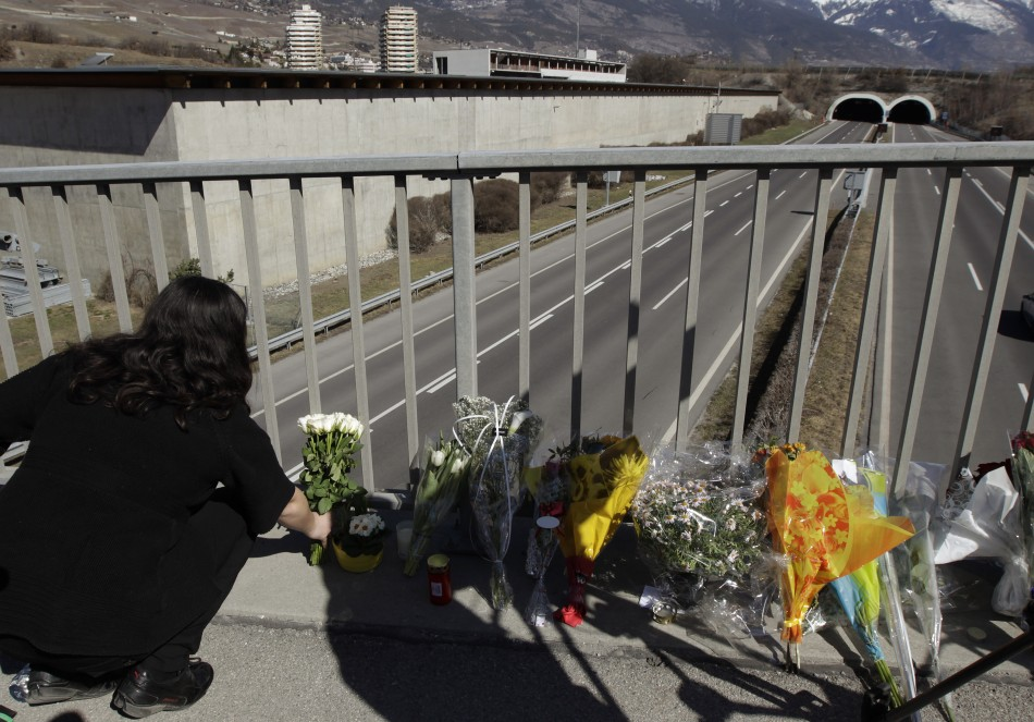 Woman places floral tributes on walkway in front of the Tunnel de Sierre following a bus crash in Sierre