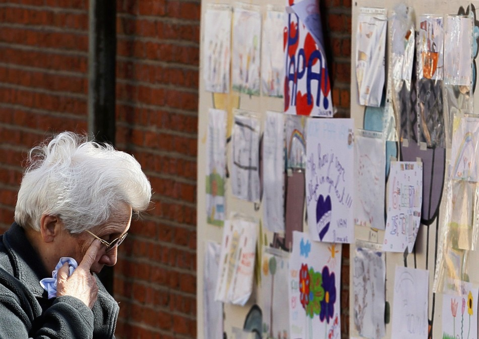 A woman, paying tribute to the victims of a bus crash in Switzerland, wipes her eyes while looking at drawings outside St Lambertus school in Heverlee