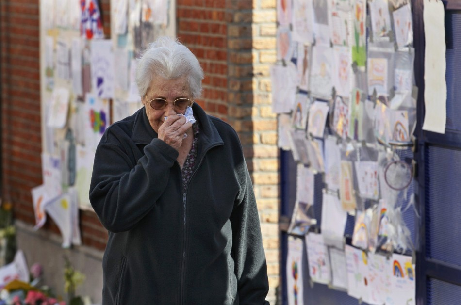 A woman, paying tribute to the victims of a bus crash in Switzerland, wipes her eyes outside St Lambertus school in Heverlee