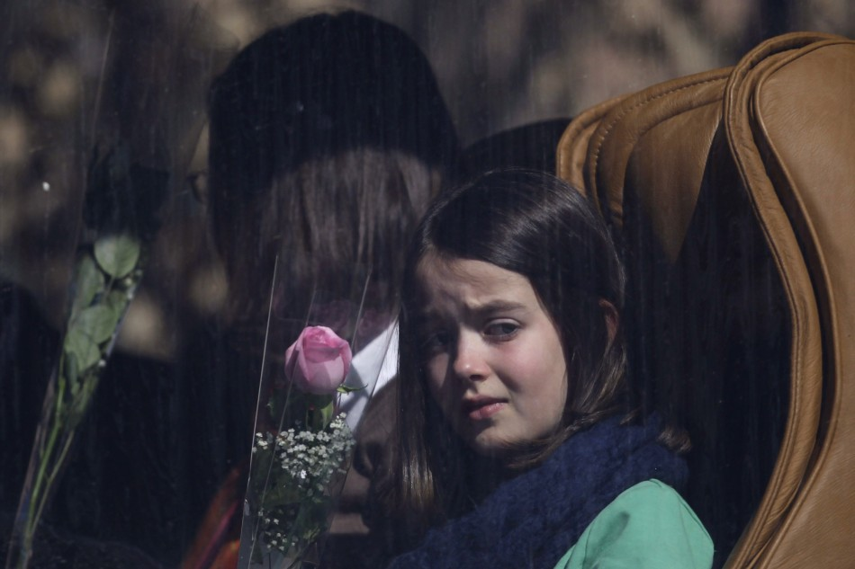 A girl holds rose while waiting in bus to visit the scene of accident at Tunnel de Sierre in Uvrier