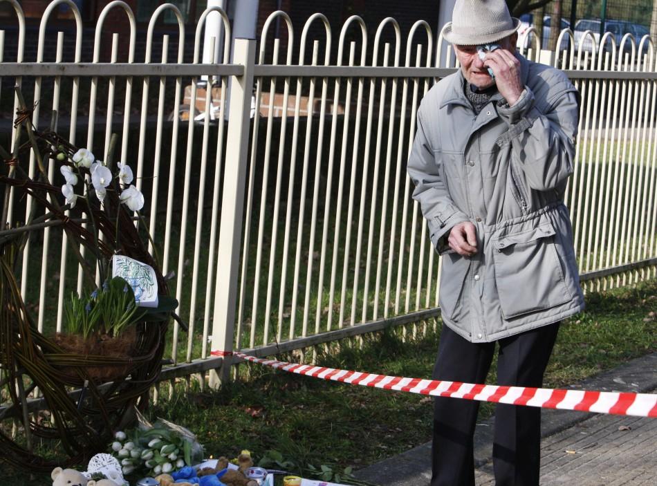 A man cries in front of the t Stekske school in Lommel