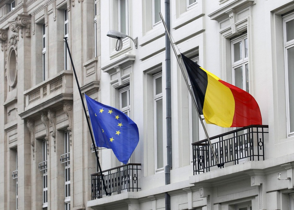 A European Union flag and a Belgian flag fly at half mast outside an official government building in Brussels