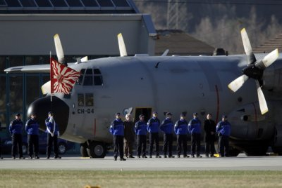 Police Cantonale du Valais officials pay the last honours to victims before the take off of a Belgian army Hercules aircraft carrying an unknown number of bodies at the airport in Sion