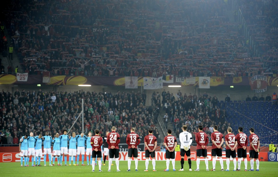 Players of Hannover 96 and Standard Liege observe a minute of silence for victims of the Switzerland bus accident in Hanover