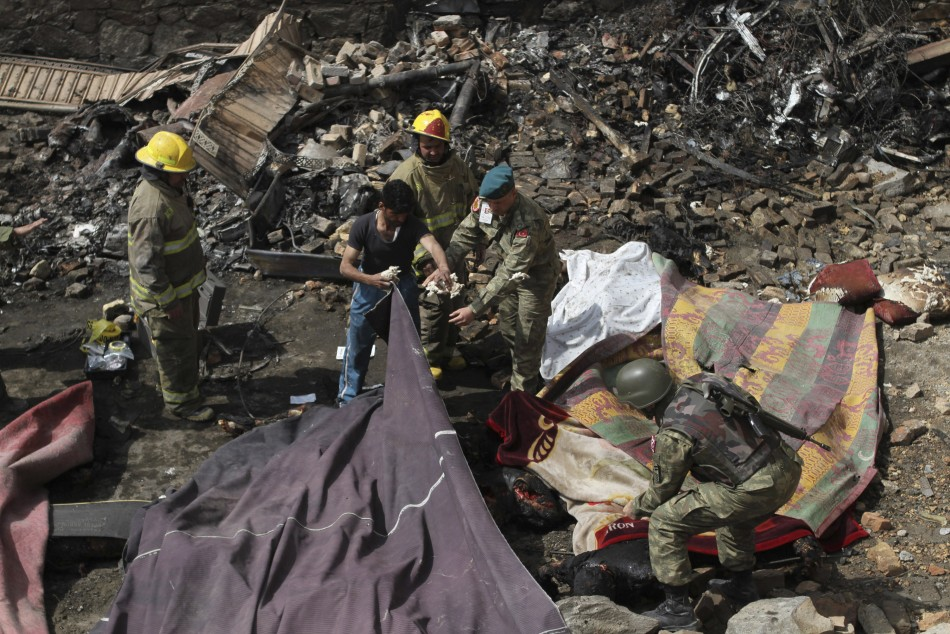 Turkish soldiers and rescue workers stand over bodies at site of Nato helicopter crash near Kabul, Afghanistan