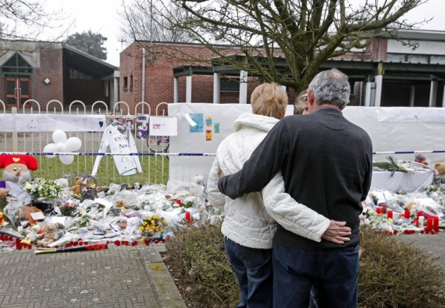 Neighbours and relatives of victims of a bus crash in Switzerland react after observing a minute of silence in front of the Stekske school in Lommel (Reuters)