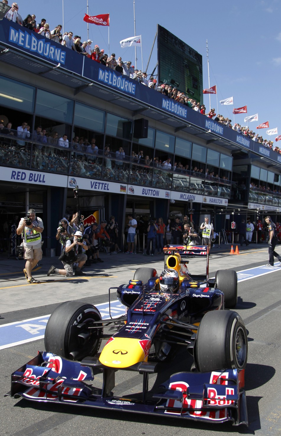 Spectators crowd vantage points as Red Bulls Vettel leaves his teams garage during the third practice session of the Australian F1 Grand Prix at the Albert Park circuit in Melbourne