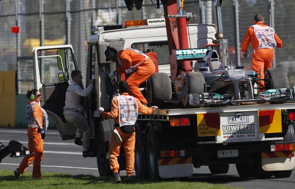 Mercedes' Schumacher climbs into the cab of a flatbed recovery truck carrying his car during the third practice session of the Australian F1 Grand Prix at the Albert Park circuit in Melbourne