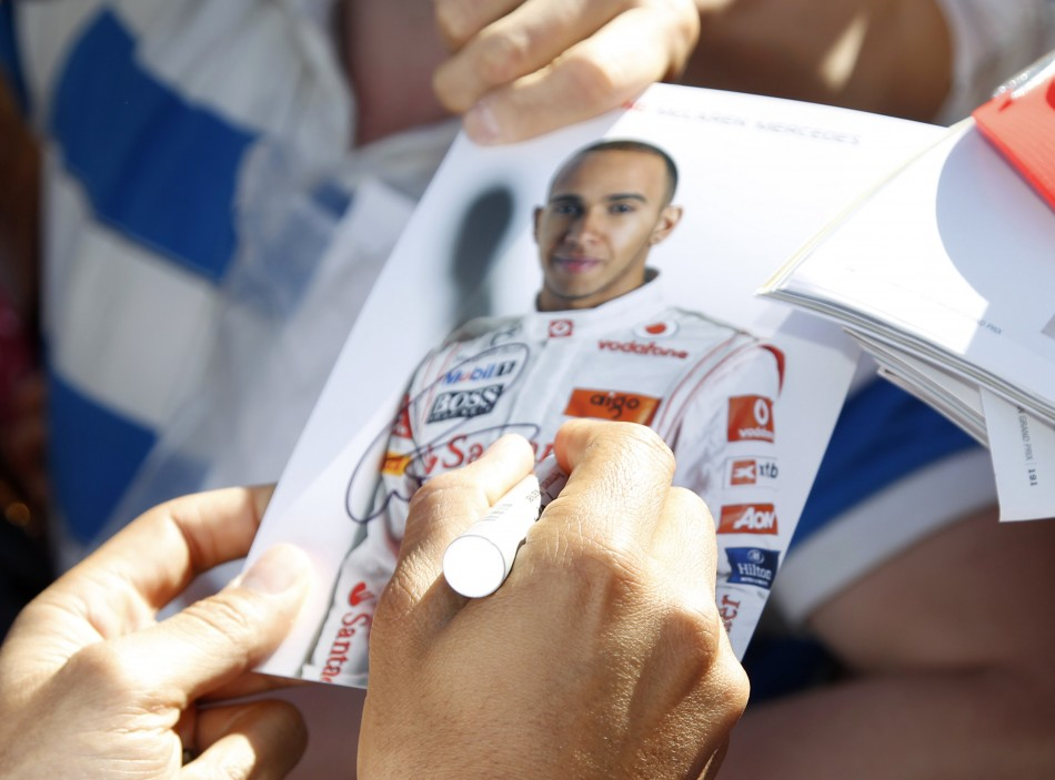 McLaren Formula One driver Hamilton signs autographs as he arrives at the Albert Park circuit for the third practice session of the Australian F1 Grand Prix in Melbourne
