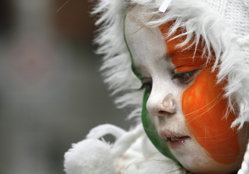 A girl with face paint in Irish national colours looks on during the Saint Patrick's Day parade along Dublin's city centre