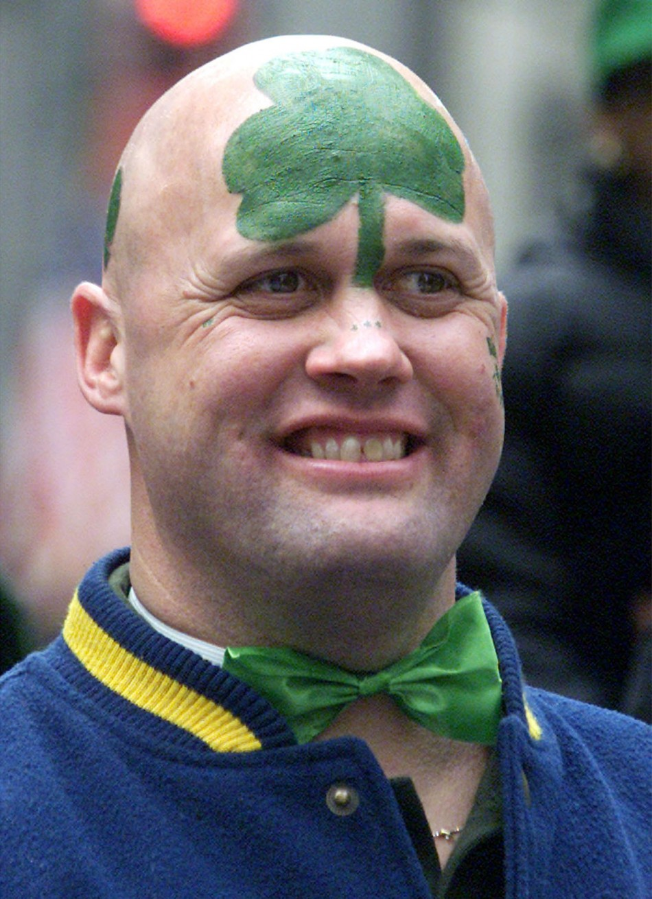 MAN WITH PAINTED HEAD WATCHES SAINT PATRICKS DAY PARADE IN NEW YORK.