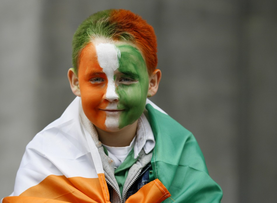 A boy, with his face painted in Irish national colours, smiles during the Saint Patrick's Day parade along Dublin's city centre