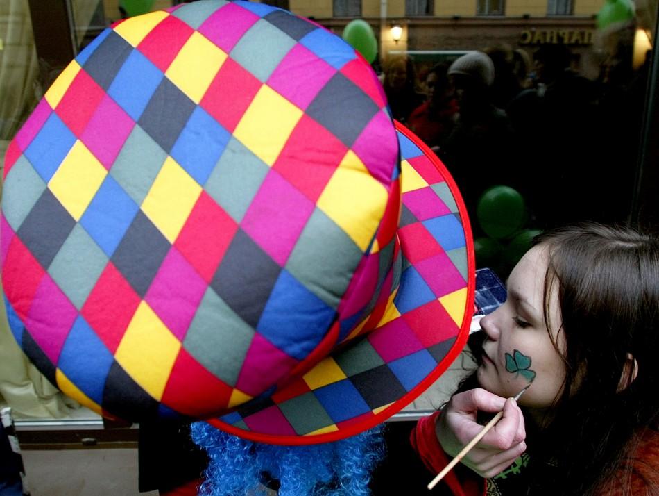 AN ARTIST PAINTS A SHAMROCK ON GIRLS FACE IN ST.PETERSBURG.