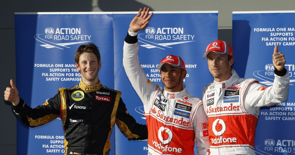 Third classified, Lotus' Grosjean, pole position McLaren's Hamilton and team mate Button wave after the qualifying session of the Australian F1 Grand Prix at the Albert Park circuit in Melbourne