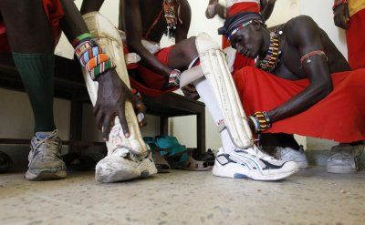 Sonyanga Ole Ngais, captain of the Maasai Cricket Warriors, assists his teammates to dress-up before their friendly match against the Jafferys team in the Kenyan coastal city of Mombasa