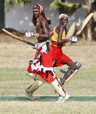 Ole Mamai of the Maasai Cricket Warriors and his teammate Ole Ngais run between the wicket against the Jafferys team during their friendly match in the Kenyan coastal city of Mombasa