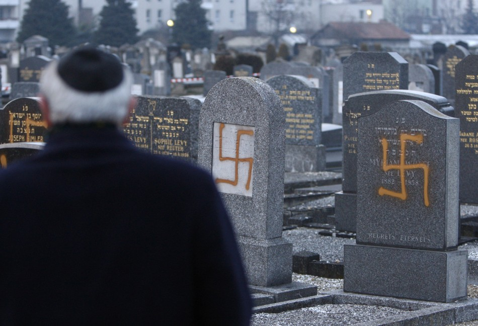 Francis Levy, head of the North Alsacian Jewish community, inspects desecrated tombstone in the Jewish Cemetery of Cronenbourg near Strasbourg,