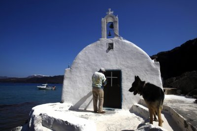 Sostis enters the Saint Nicolas church on the volcanic islet of Palaia Kameni located in the caldera of Santorini