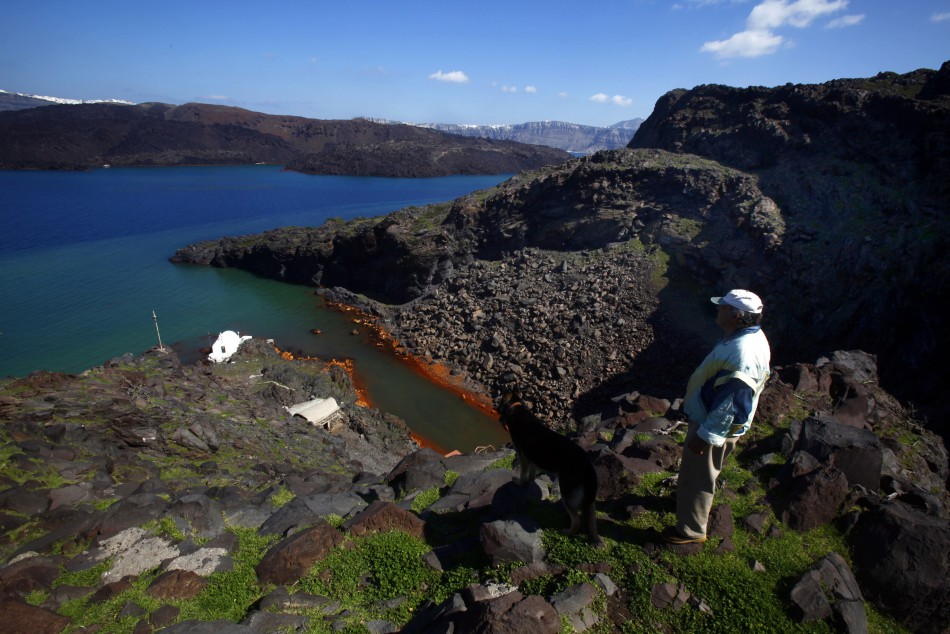 Sostis walks his dog Plato on the volcanic islet of Palaia Kameni located in the caldera of Santorini