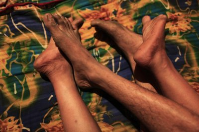 Feet belonging to Hashi, a prostitute, and Babu, her husband, are seen inside her small room at Kandapara brothel in Tangail, a northeastern city of Bangladesh