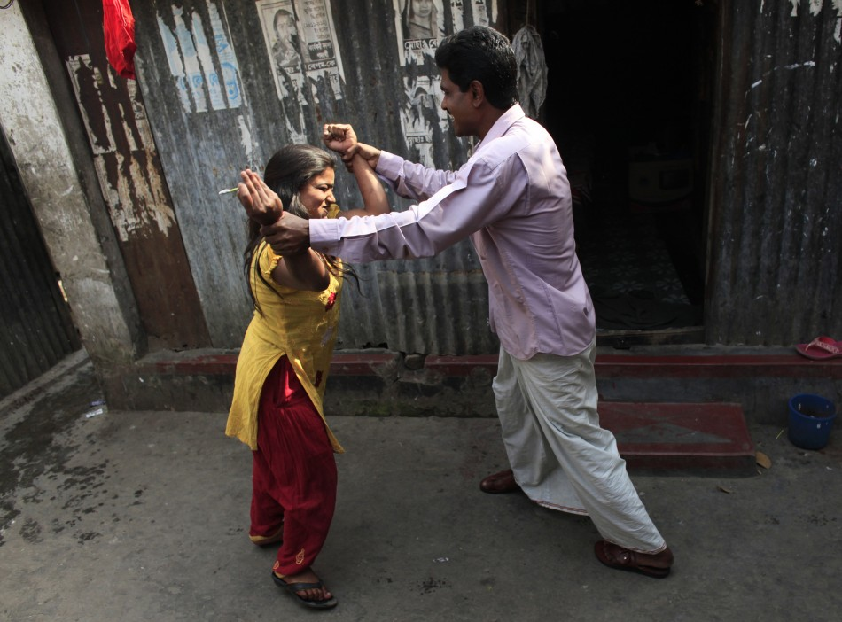 A customer jokes with seventeen-year-old prostitute Hashi as she tries to grab him into her room at Kandapara brothel in Tangail, a northeastern city of Bangladesh