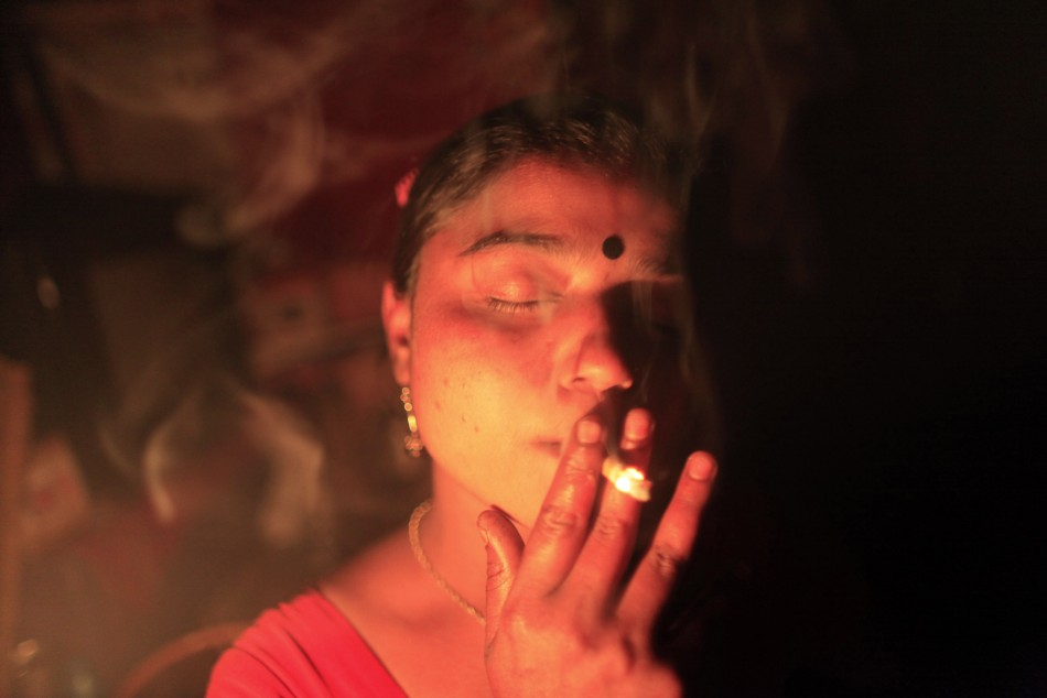 Seventeen-year-old Hashi smokes a cigarette inside her room before she serves a customer at Kandapara brothel in Tangail, a northeastern city of Bangladesh